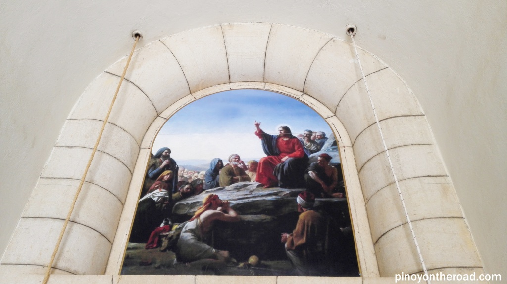 A painting depicting Jesus preaching His disciples is displaced above the main entrance door of the Church of Mt Beatitudes